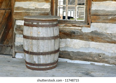 Old water barrel on the porch of a log cabin.