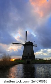 Old water mill beside a canal of the Eilandspolder in sunset, the Netherlands