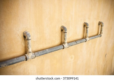 Old water pipes in front of wall