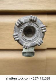 old water spigot closeup on a vinyl wall