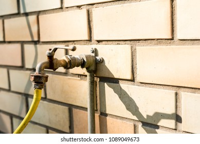 Old water tap with yellow hose, concept image with copy space