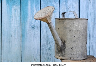 old watering can on wooden background
