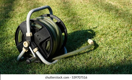 The old watering rubber pipe for gardening was rolled in the white wheel reel equipment for tidy, put on the green grass lawn field in the backyard