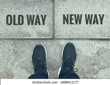 Old way or new way choice; text on  ground, feet and shoes on floor, personal perspective footsie concept
