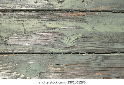 Old weatherboard painted with duck egg blue paint. The weatherboard is old and the paint cracked and faded.
