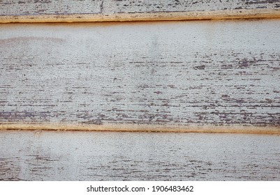 old weatherboard wall with peeling white paint
