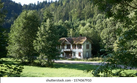 Old weathered abandoned home in forest clearing on beautiful sunny day deep in the Black Forest of Germany.
