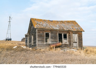 An old weathered abandoned homestead farm sits decaying and falling apart in the plains of northeast Montana.