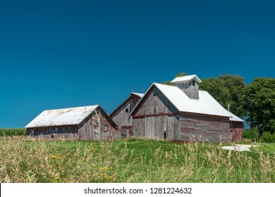 Old, weathered barn resting in a rural setting in the Midwest.  Clear, blue sky background for the red barn, corn crib and outbuildings.  Green grass and trees in the scene