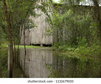 Old weathered barn and trees are reflected in a puddle of water