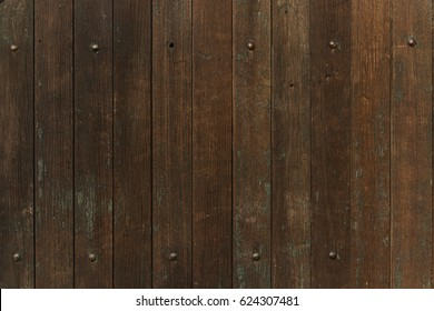 Old weathered and damaged brown wooden door background or texture