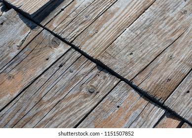 Old weathered dark brown wood on a boardwalk made from different size pine wood with knots, with a diagonal line from connecting plates