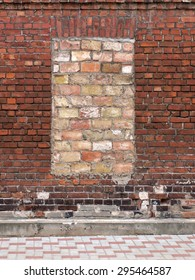 Old weathered dark red brick wall with bricked up window.