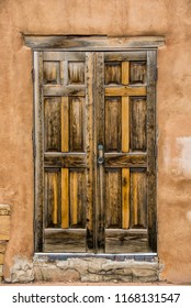 An old weathered door opens into a southwestern building of stone and stucco.