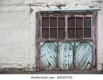 Old weathered door with pale turquoise and pink paint in southwestern style