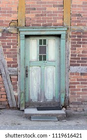 Old, weathered, green wooden door in a half-timbered house with red bricks