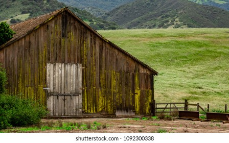 An old weathered moss covered barn stands on a hillside in Salinas Valley of Monterey County, in central California.