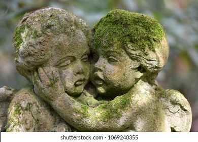 An old, weathered and moss covered sandstone culpture of two angels that comfort each other.