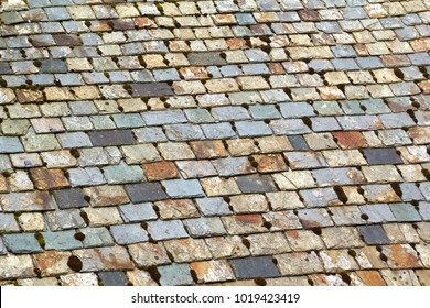 Old weathered multi coloured roof slate tiles full frame