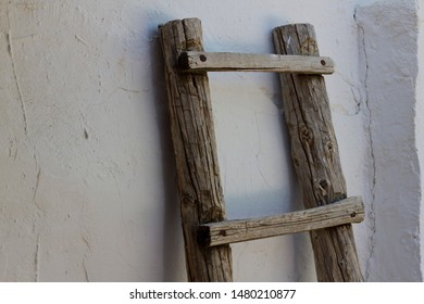 Old weathered olive grove ladder against a Spanish white washed wall