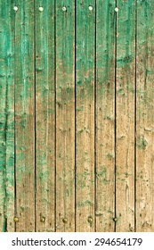 Old, weathered planks partly covered with green paint.