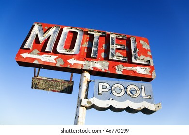 Old weathered retro neon motel sign advertising pool and vacancy. Horizontal shot.