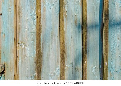 Old weathered rustic barn wood wall with green paint - peel-off - closeup of board wall with shadows and natural pattern