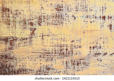 Old weathered rusty metal surface with yellow and blue paint peeling off