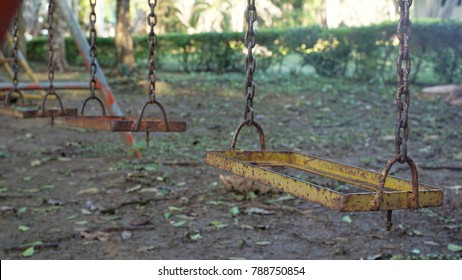 Old weathered rusty swing set in neglected playground.