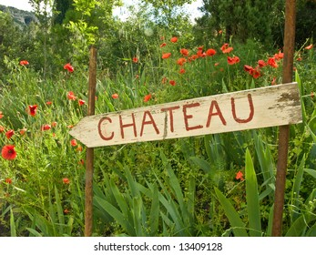 Old weathered signpost to Chateau with background of poppies, France