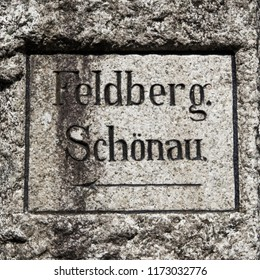 old weathered signpost made of stone with German designation to Feldberg and the city Schönau in the Black Forest