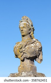 Old weathered stone bust of Marianne, a symbol of  France and the French Republic, allegorical of Freedom and Reason, covered in colorful lichen against a blue sky