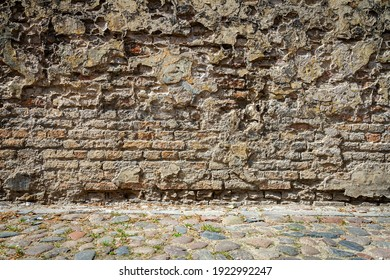 Old weathered wall of bricks and a cobblestone