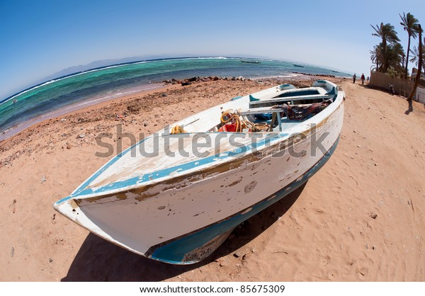 Old weathered white boat on the egyptian beach