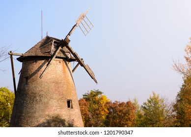 An old weathered windmill in the fall of the autumn in the sun.