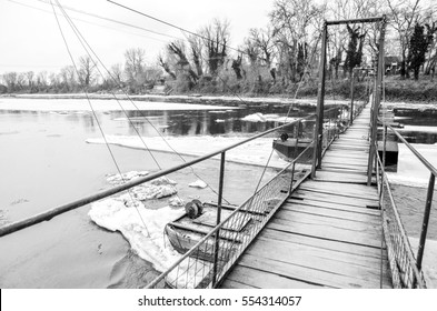 Old weathered wood plank suspension footbridge over river in the winter. Back and white. Monochrome