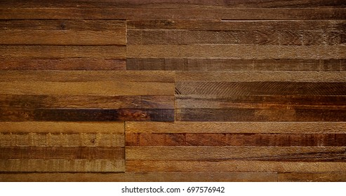 Old weathered wood surface with long boards lined up. Wooden planks on a wall or floor with grain and texture. Dark neutral brown tones with contrast.