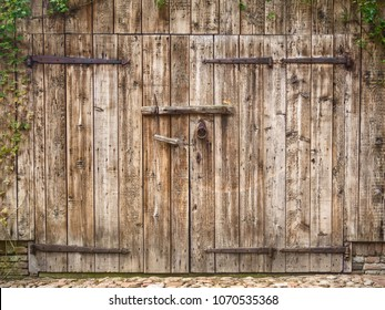 Old weathered wooden barn door with steel hinges
