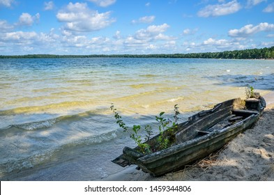 Old weathered wooden fishing boat left on the lake shore