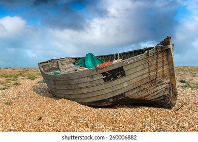 An old weathered wooden fishing boat under a blue sky on a shingle beach