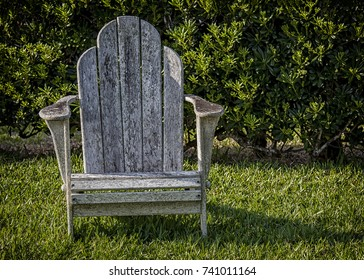 Old weathered wooden lawn chair.
