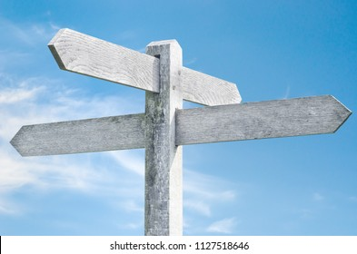 Old weathered wooden signpost against blue sky with four sign choices pointing in different directions.