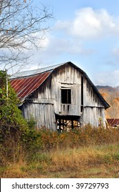 Old weathered and worn wooden barn stands surrounded by Autumn foliage.  Ozark Mountains stand in background.