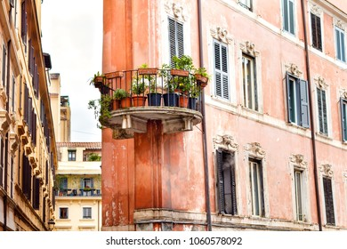 Old, weathered, yet charming building with a circular balcony and flower pots in Roma city center, Italy.