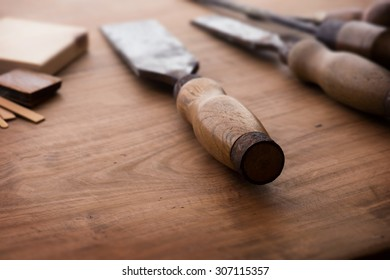Old and well used wood working chisels, on a old workbench. Old chisel with an oak handle. Shallow depth of field.