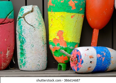 Old well used and worn out colorful lobster floats and lobster buoys found along down east Maine coast