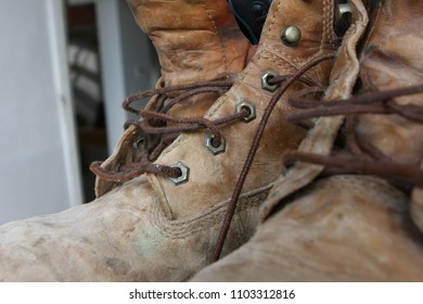 Old well-worn dirty work boots untied