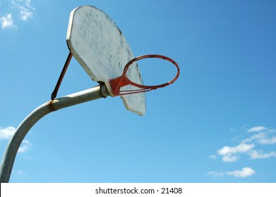 Old, well-worn school-ground basketball hoop (without net) against a sunny, bright, blue sky.