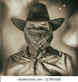 Old West Cowboy Bandit 2. Old west bandit outlaw with covered face and cowboy hat, edited in vintage film style.