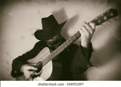 Old West Cowboy Playing Guitar. A cowboy playing a guitar, edited in vintage film style.